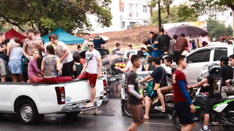 farang and thais on pickup truck wetting people on motorbikes Footage