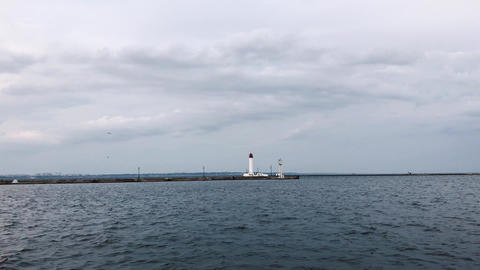 Seagulls fly over the lonely lighthouse. Cloudy weather. Sea Port of Odessa ビデオ