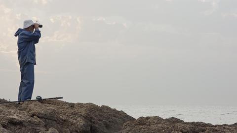 Old fisherman looking into the ocean using his binoculars Footage
