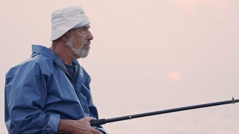 Old fisherman standing on sea side rocks and fishing against the sunset GIF