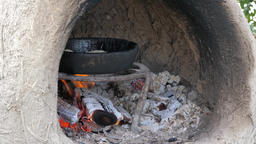 Pancake bread is baking on a clay pan in a traditional dome oven Footage