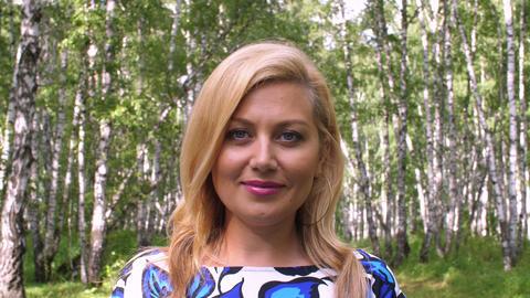 Portrait smiling blonde woman in summer birch grove close up ビデオ