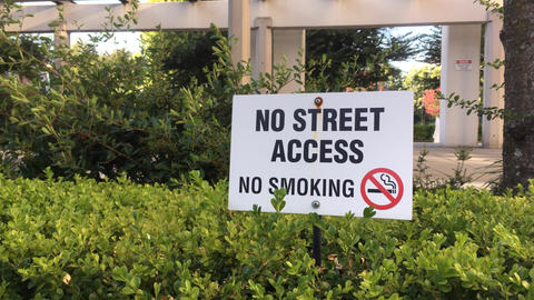 Motion of no street access and no smoking sign on grass with 4k resolution Footage