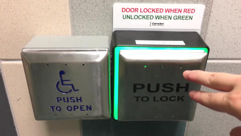 Motion of woman pressing open button for handicap using washroom with 4k Footage