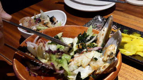 Motion of people eating oyster seafood salad on table inside Japanese restaurant Live Action