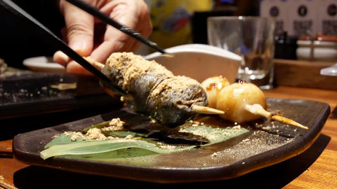 Motion of people eating Japanese style grilled dango barbeque and sesame sauce Live Action