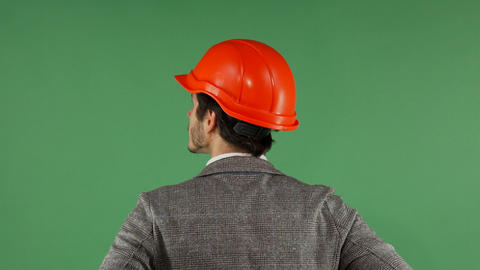 Rear view portrait of a contractor wearing hardhat looking at the green screen Footage