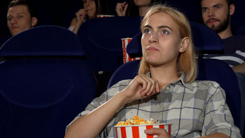 Attractive female eating popcorn at movie premiere at the cinema Live Action