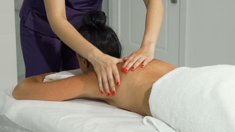 Professional masseuse massaging back and shoulders of a client Live Action