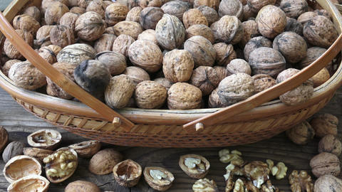 Walnuts in a basket on a wooden background Footage