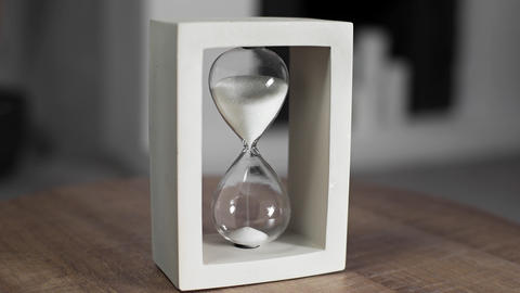 Hourglass with white sand is measuring time, sand in the sandglass, hourglass is ビデオ