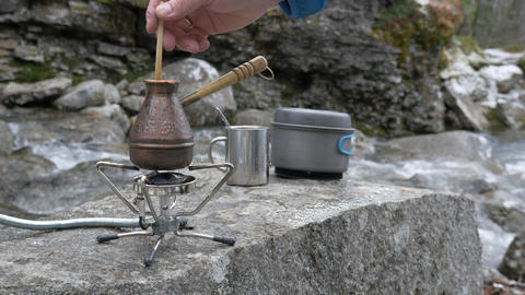 On a portable gas burner, there is a kettle for brewing coffee. Sugar is thrown Footage