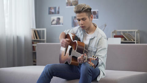 College guy enjoying melody for his new song, talented teenager playing guitar Footage