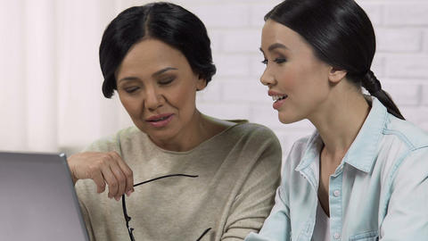 Adult daughter teaching mom to use computer, helping to register on website Live Action