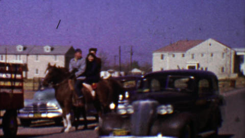1955: Family crossing street riding horse as classic car drives by Footage