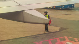 Airport Worker Walks under Plane Wing on Airfield Footage