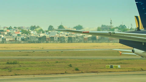 Aircraft Moves along Runway by Field Houses Footage