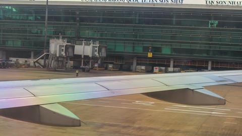 Passenger Loading Bridge behind Airliner Wing on Airfield Footage
