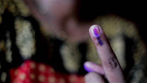 Close shot of young Indian voter cast her vote and showing finger as proof Footage