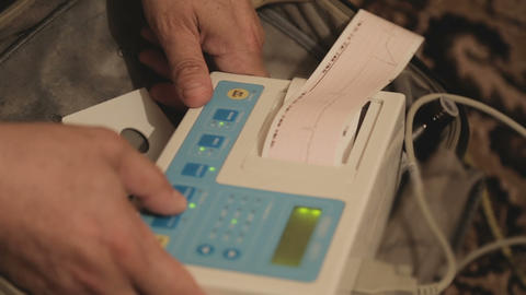 Male clinic worker operating cardiogram machine, ischemic disease, heart rate Footage