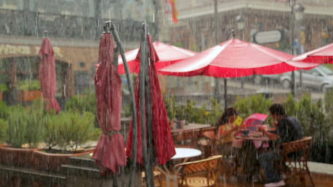 Couple having lunch on cafe terrace, romantic date under rain, relationship Footage