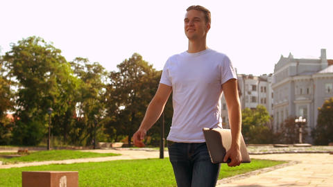 student with computer walks outdoors Live Action