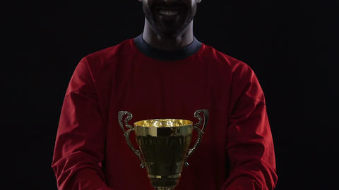 Professional male soccer player holding golden victory cup in hands, achievement Live Action