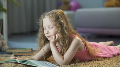 Smart little girl reading favorite book at home on her own, happy childhood Footage