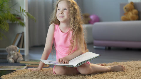 Happy smart young girl reading book at home, enjoying childrens literature Footage