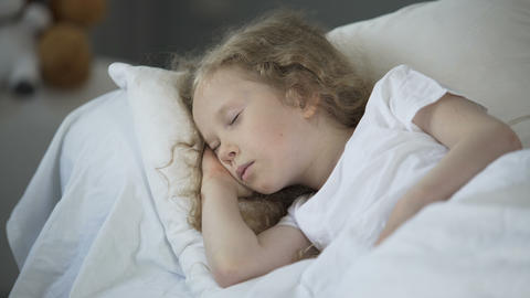 Blond little girl sleeping in comfortable bed at home, calm rest for good health Footage