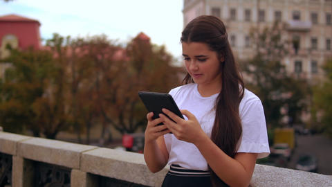 girl use touch screen tablet outdoors Live Action