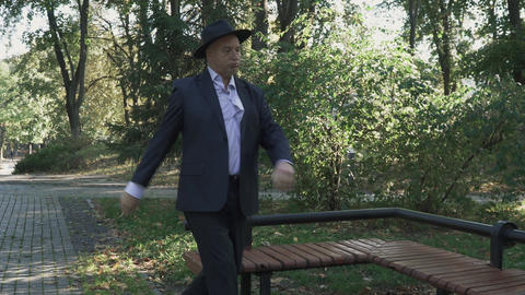 Old man in a business suit drunk in the park Live Action