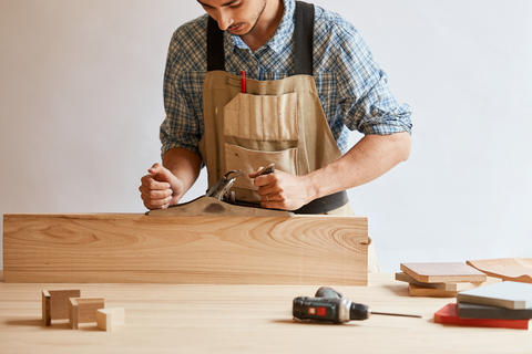 carpenter working with wood using plane against white wall in studio フォト