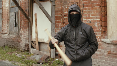 Hooliganin black mask and jacket with hood holds in baseball bat on street Live Action