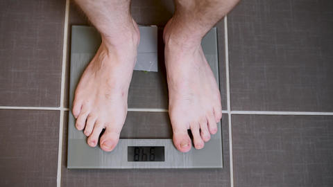 Male feet on glass scales, men's diet, body weight Footage