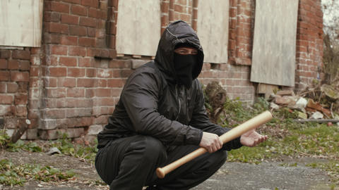 Bandit man in black mask and jacket with hood with baseball bat sits on street Live Action