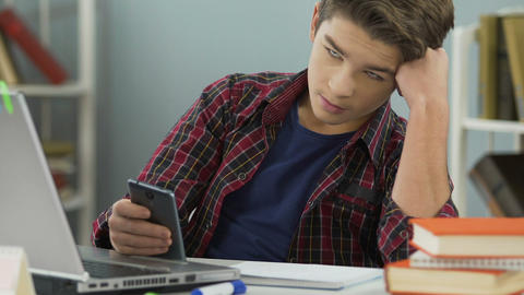 Bored school pupil looking indifferently at homework books, surfing internet Live Action