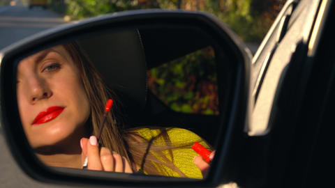 Woman paints her lips with red lipstick and looks in the rear-view mirror Footage