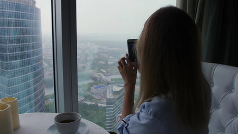 Woman makes a picture of rainy moscow view on cellphone sitting in coffee shop Footage