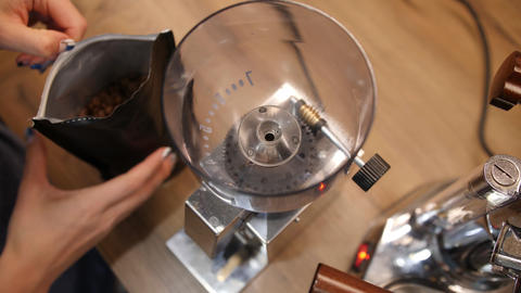 Fimale barista fills modern electric grinder with brown coffee beans. High angle Footage