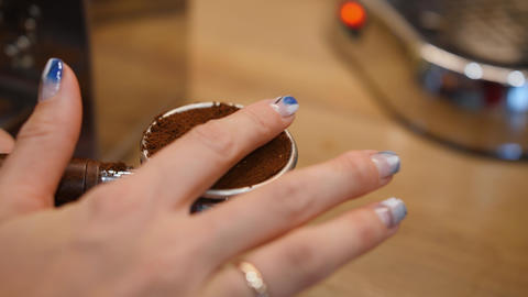 Woman levels ground coffee with her finger in filter holder for coffee machine Live Action