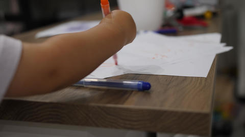 Close up shot of drawing kid. Baby scribblings made with orange marker GIF