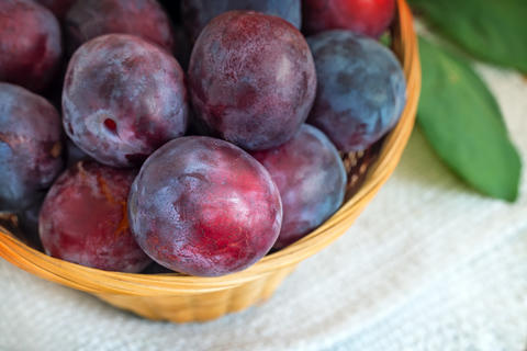 Large ripe plums in a wicker basket Photo