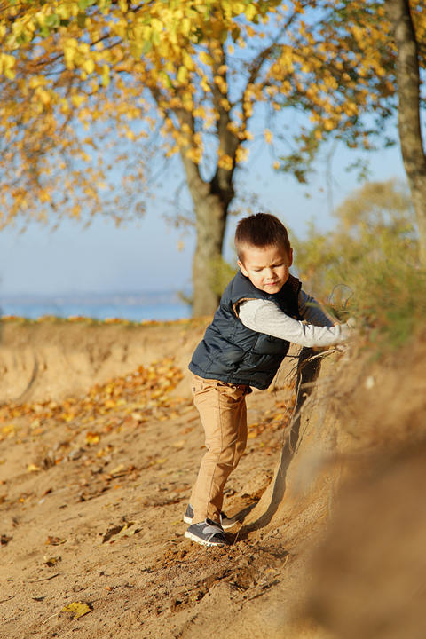 A small child very carefully walks along the shore フォト