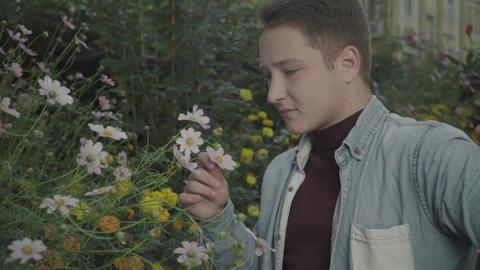 Feminine guy sniffs flowers Live Action