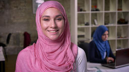 Sweet nicely smiling arabian female is standing in her pink hijab and smiling at Footage