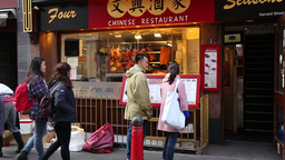 Asian couple looing at menu at Chinese restaurant Chinatown London UK Footage