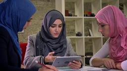 Gorgeous hijab muslim women are sitting at workplace, holding tablet they have Footage