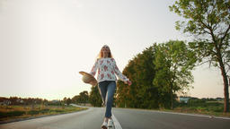Beautiful young female with nice hat smiling and running on asphalt road while Footage