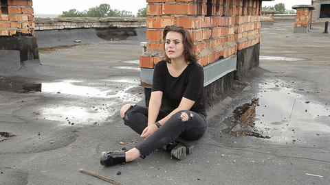 Teen girl in depression sitting on the roof of a building Archivo